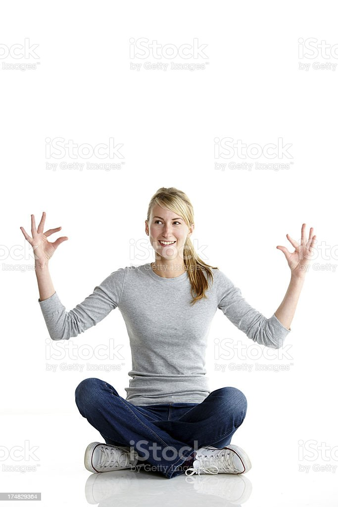 Young woman sitting on the floor attempting yoga pose royalty-free stock photo