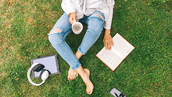 Young woman sitting on the grass drinking coffee and reading a book enjoys outdoor recreation.