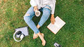 istock Young woman sitting on the grass drinking coffee and reading a book enjoys outdoor recreation. 1137366043