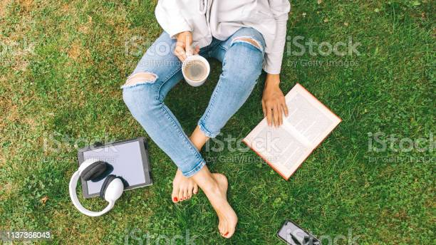 Young woman sitting on the grass drinking coffee and reading a book picture id1137366043?b=1&k=6&m=1137366043&s=612x612&h=n 5msbtz95 v9verzgqwvln49ryetinc6ijlqyymhc8=