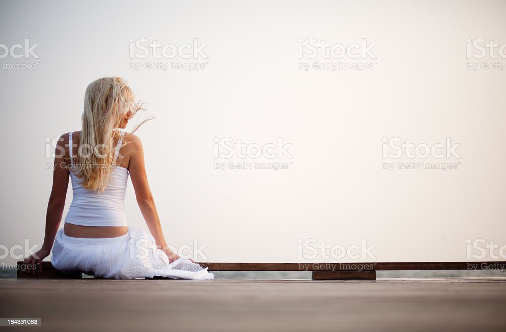 Young woman sitting on the pier stock photo