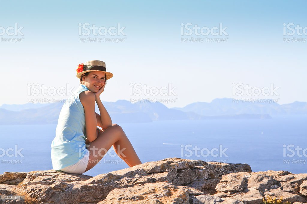 young woman sitting on the rocks next to the sea stock photo