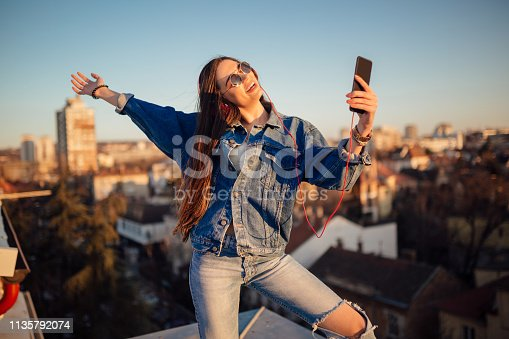 Young woman on the rooftop, taking a selfie during sunset