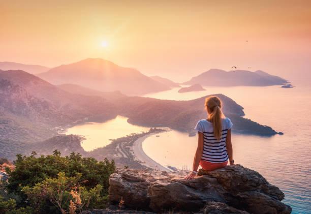 Junge Frau sitzt oben auf Felsen und Blick auf das Meer und die Berge an farbenprächtigen Sonnenuntergang im Sommer. Landschaft mit Mädchen, orangefarbenen Himmel mit Sonne, Meer und Bergrücken. Oludeniz, Türkei. – Foto