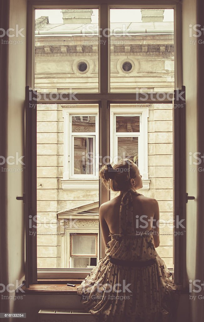Young woman  sitting on the window stock photo
