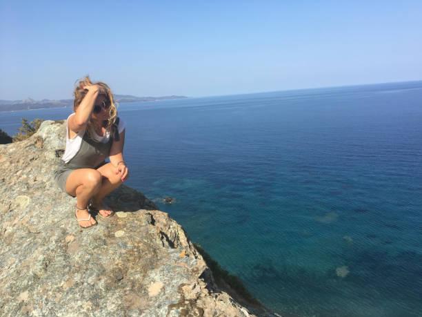 jeune femme assise au sommet d'une falaise - randonnée corse photos et images de collection