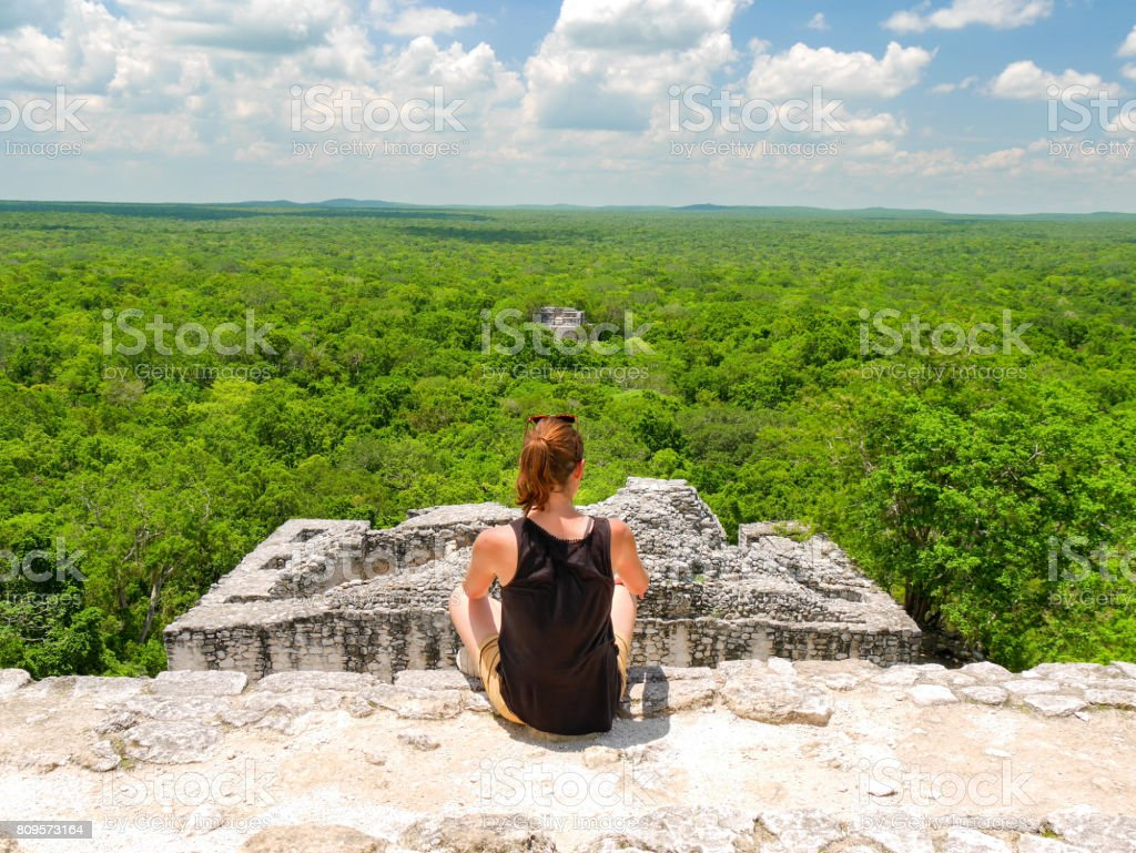 Young woman sitting on top of maya temple ruin calakmul in mexico stock photo