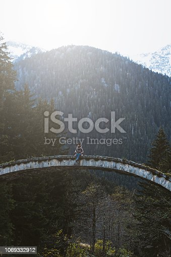 Young woman sitting on top of the stone bridge over river near mountainside, Çilanç Bridge, Rize