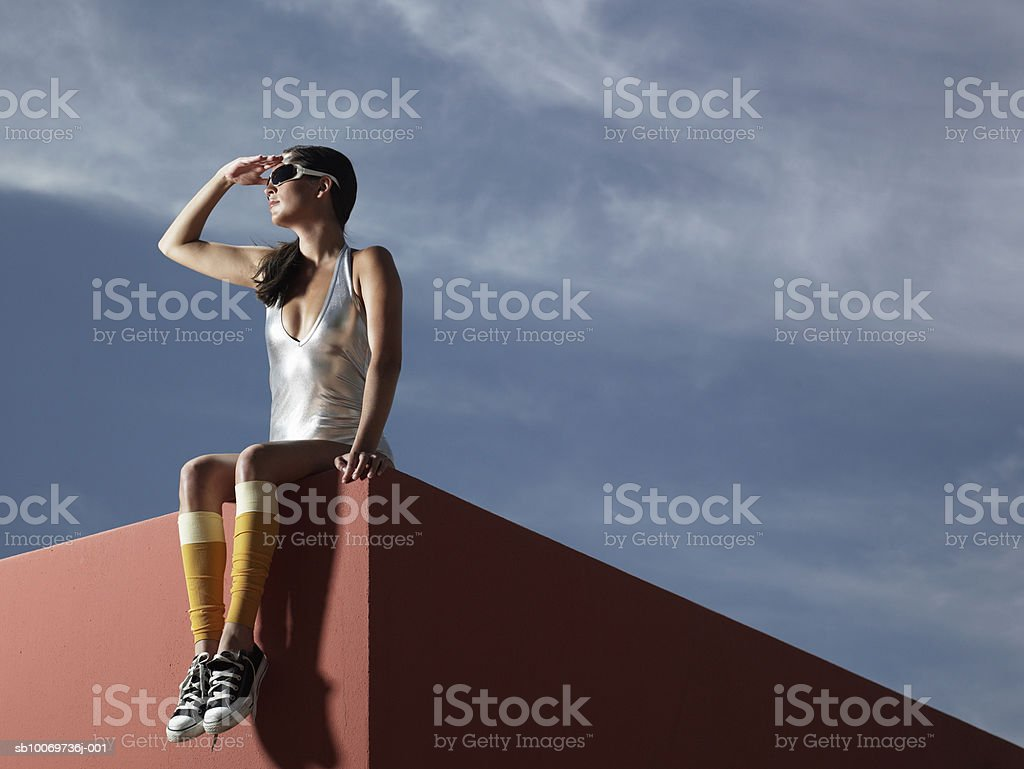 Young woman sitting on wall, low angle view royalty-free stock photo
