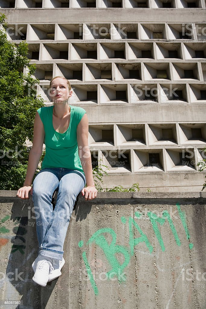 Young woman sitting on wall royalty-free stock photo