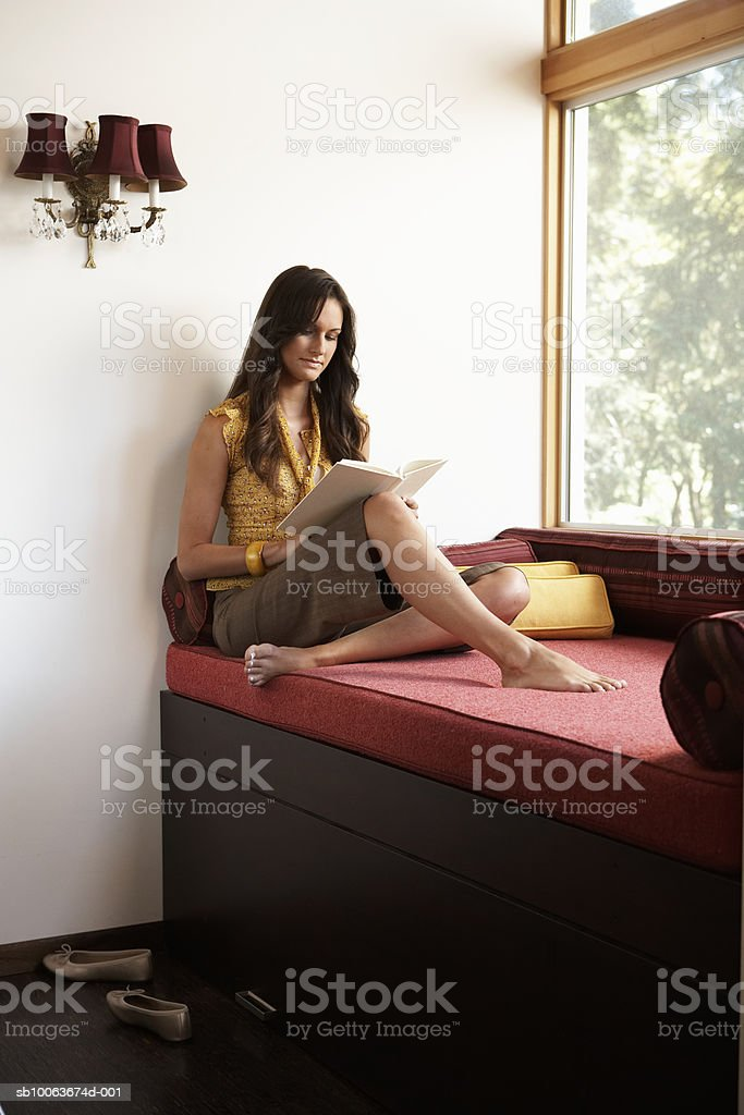 Young woman sitting on window seat reading royalty-free stock photo