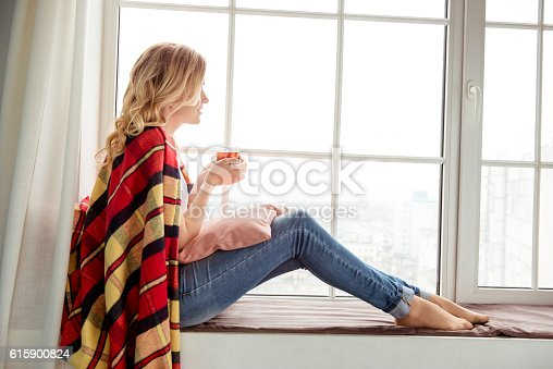 istock young woman sitting on windowsill and basking with plaid 615900824