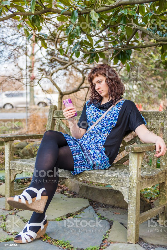 Young woman sitting on wooden bench in winter garden by road looking at phone stock photo