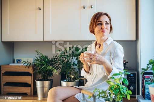 A young woman with white night shirt sitting on worktop indoors in kitchen, holding a cup of coffee.