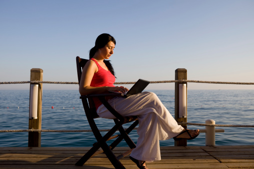 istock Young woman sitting outdoor and using laptop 183756313