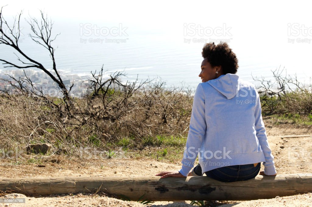 Young woman sitting outdoors on a log stock photo