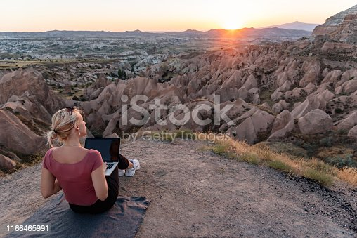 Young woman sitting outdors with laptop during sunset.