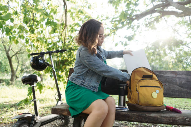 Young woman sitting outside and putting laptop in backpack stock photo