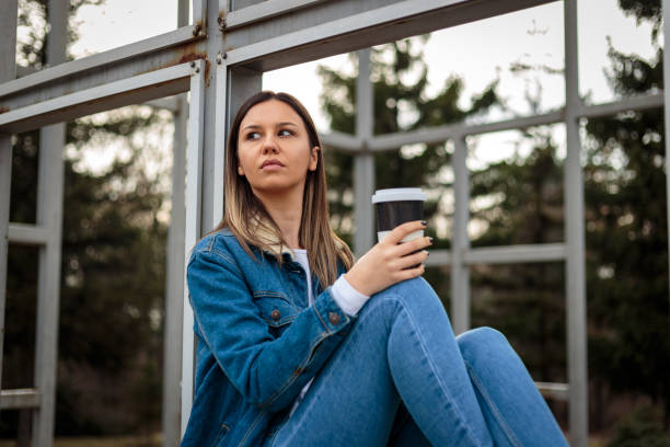 Young woman sitting outside drinking coffee and listening to music stock photo