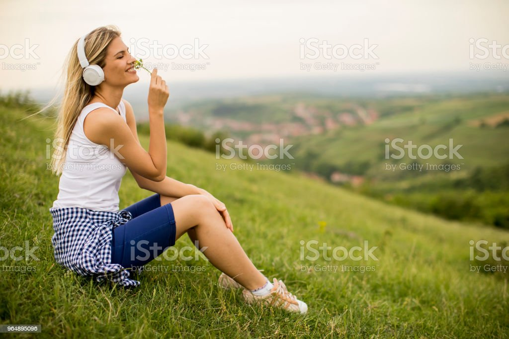 Young woman sitting outside on grass and listening to music on headphones royalty-free stock photo