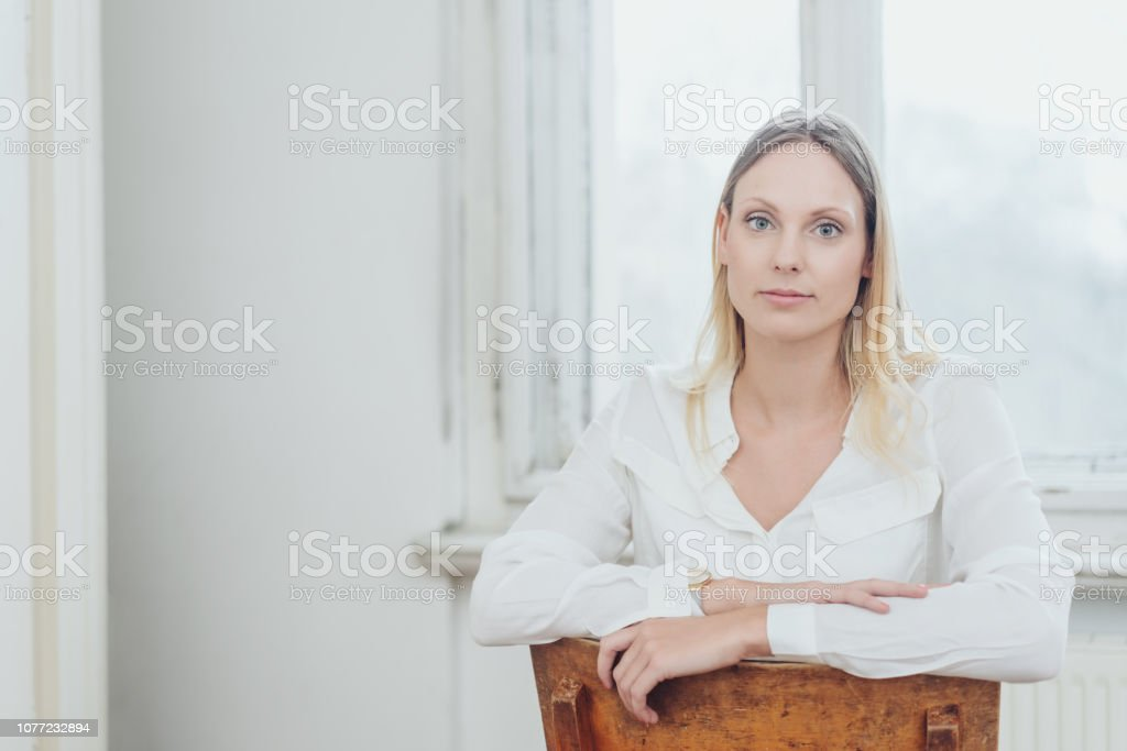 Young woman sitting staring at the camera