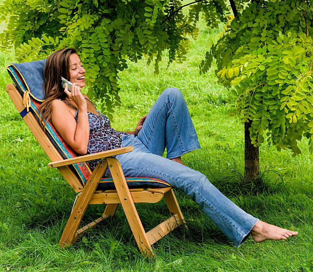 Young woman sitting under tree using mobile stock photo