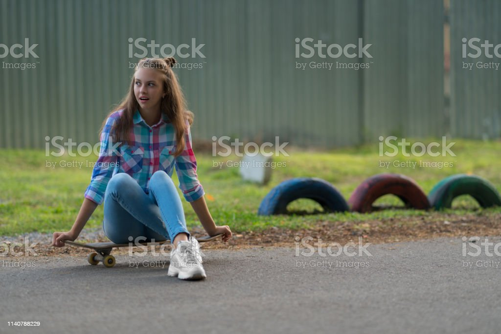 Young woman sitting waiting on a skateboard on an urban road looking...