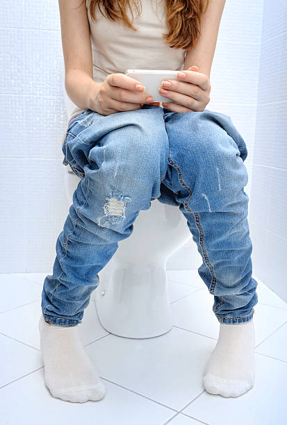 young woman sitting  wc toilet bowl using phone in hands . - cell phone toilet stockfoto's en -beelden