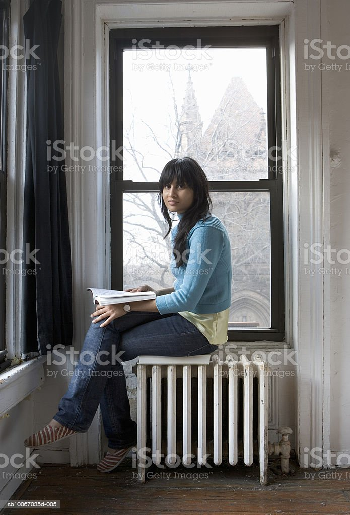 Young woman sitting with book by window, portrait foto de stock libre de derechos