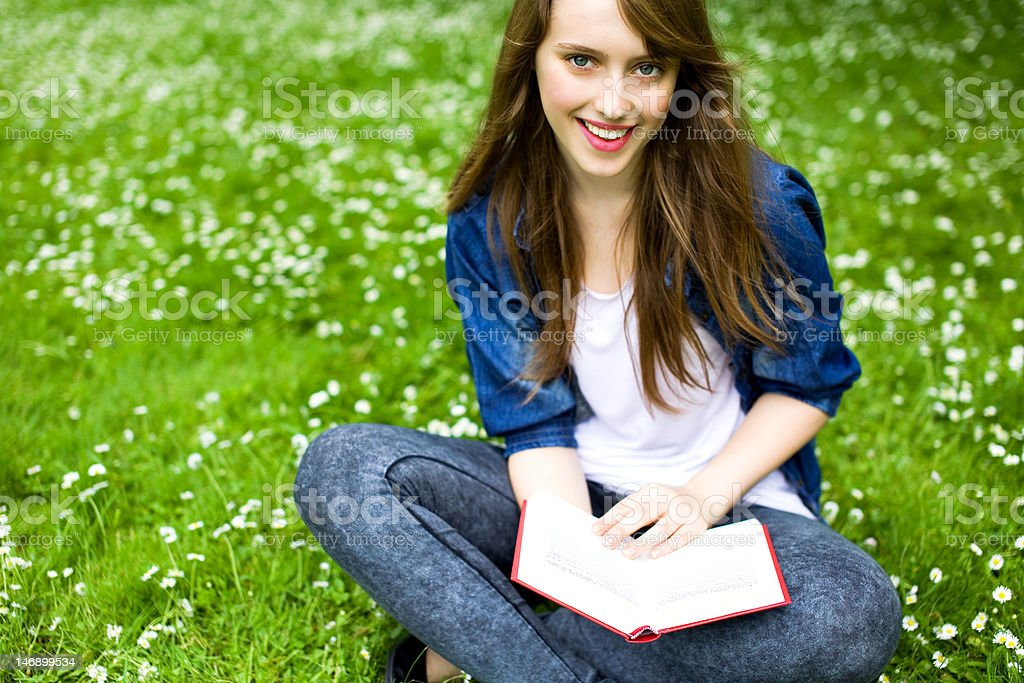Young woman sitting with book on grass royalty-free stock photo