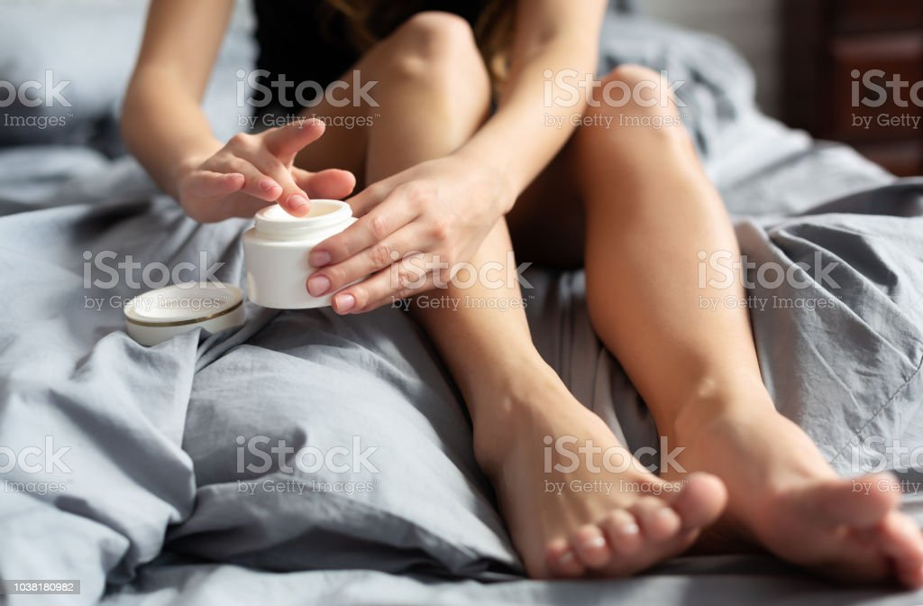 Young woman sitting with cream for feet stock photo