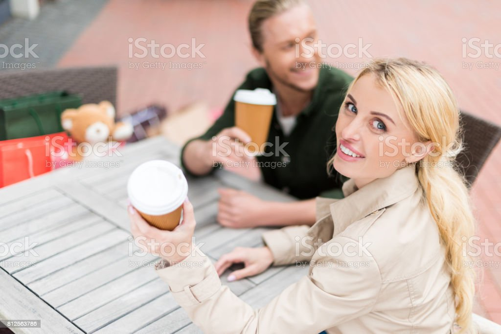 young woman sitting with her boyfriend while drinking disposable coffee at cafe stock photo