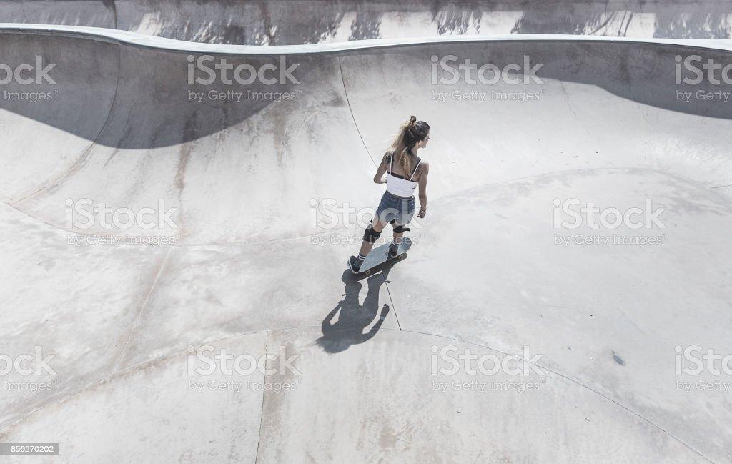 Young woman skateboarding in skateboard park stock photo