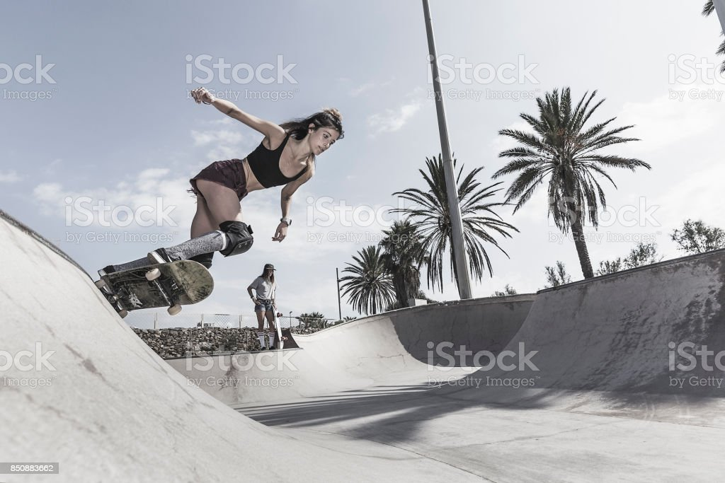 Young woman skateboarding in skatepark stock photo