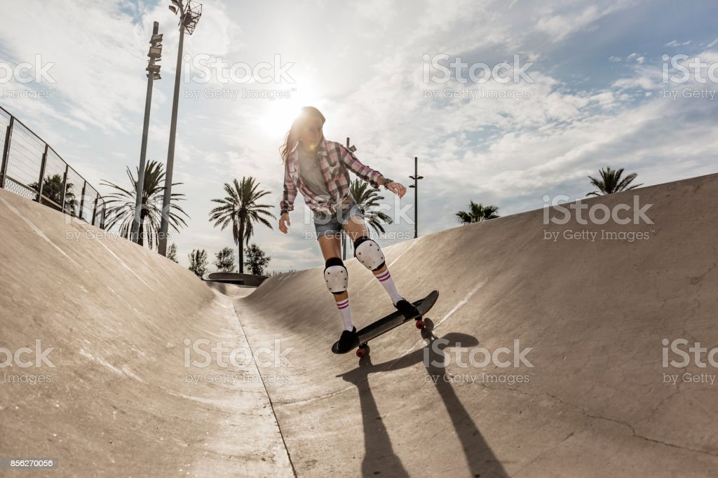 Young woman skating in skateboard park stock photo