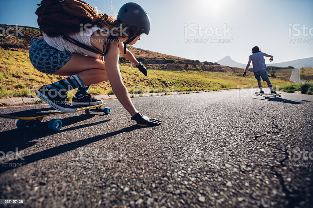 Young woman skating with her friend stock photo