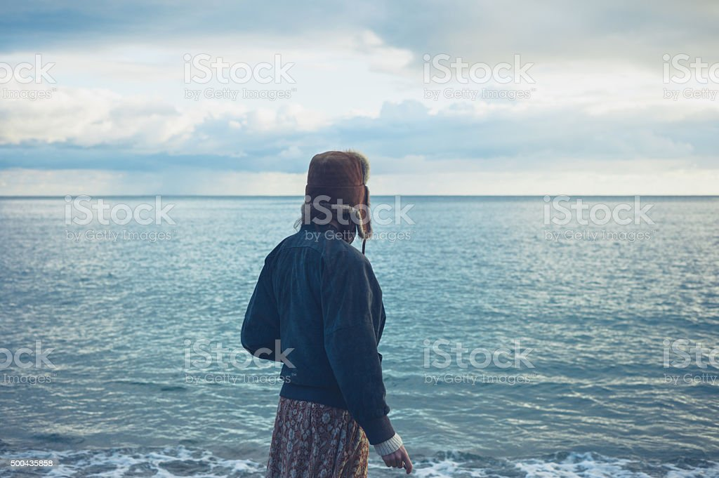 Young woman skimming stones by the sea stock photo