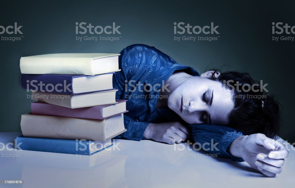 Young woman sleeping collapsed next to books in moody shot stock photo