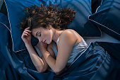 istock Young woman sleeping in bed at night 1289222246