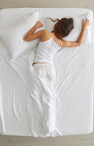 Young woman sleeping in bed Woman lying in bed face down stock pictures, royalty-free photos & images