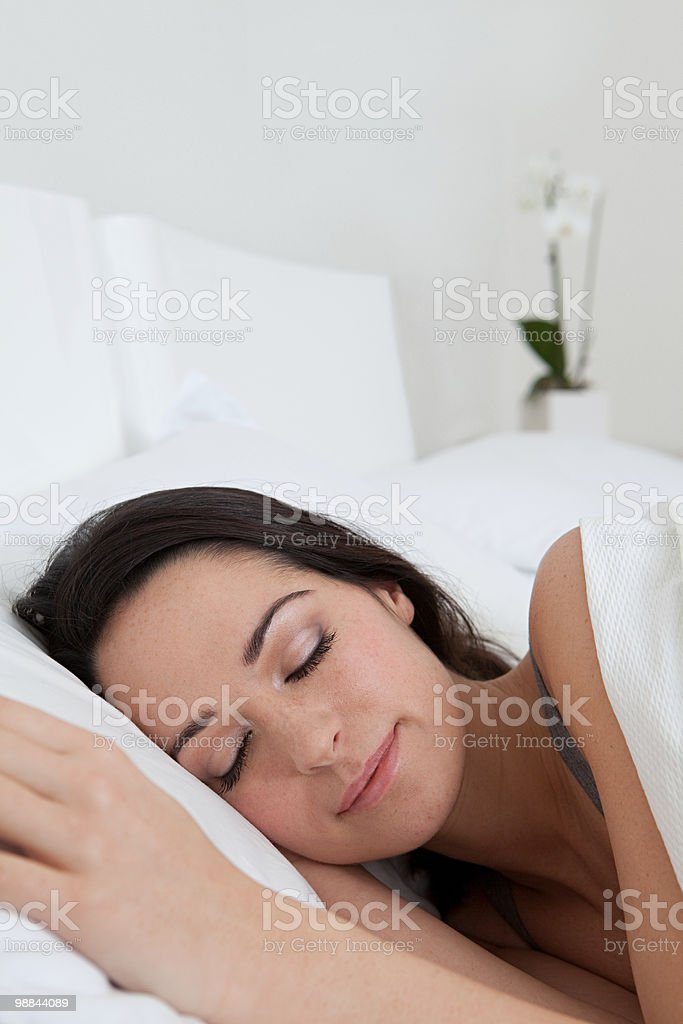 Young woman sleeping in bed royalty free stockfoto