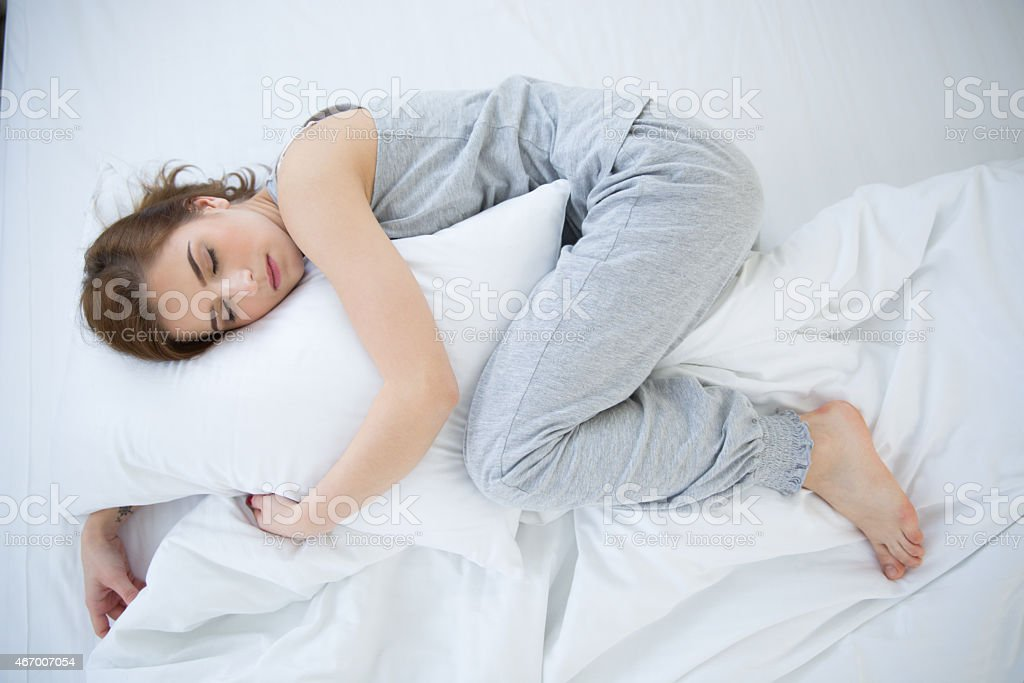 Young woman sleeping in fetal position stock photo