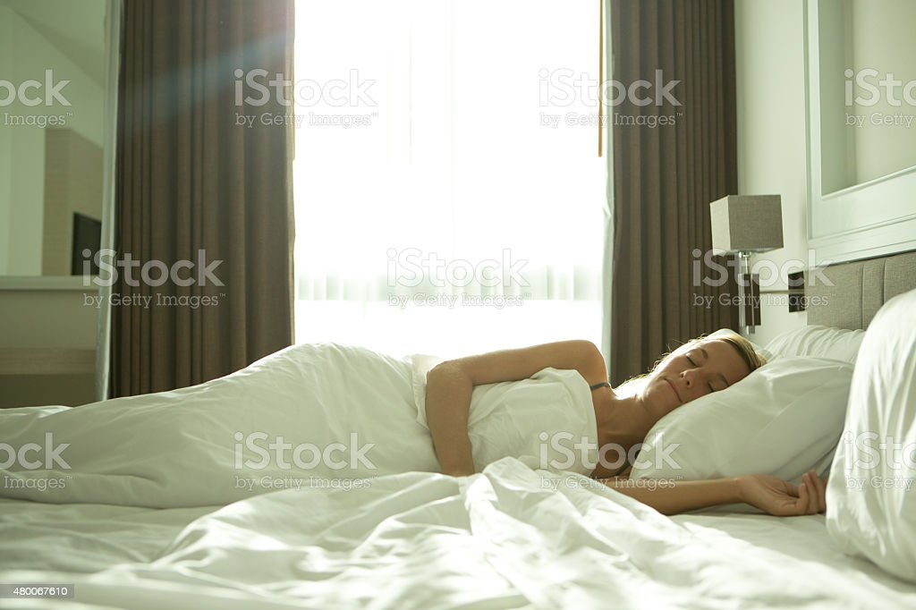 Cheerful young woman sleeping in her hotel room.