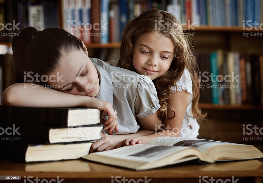 Young Woman Sleeping in Library and Little Girl Reading Book royalty-free stock photo