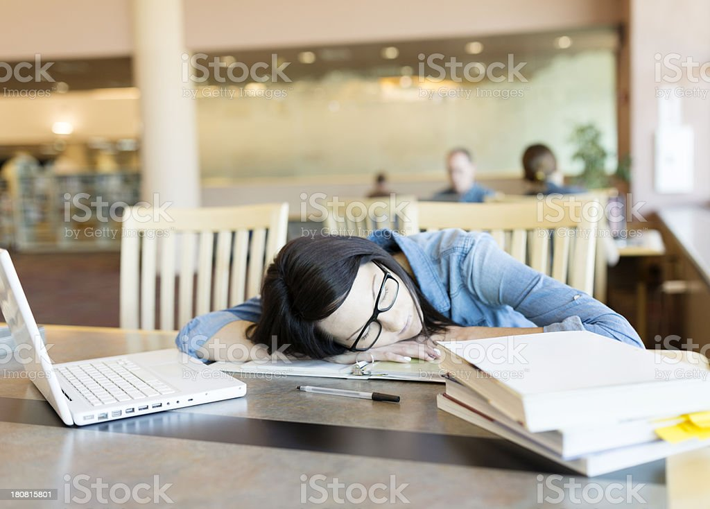 Young woman sleeping in library while studying stock photo