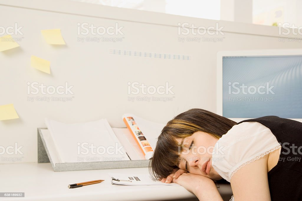 Young woman sleeping in office cubicle stock photo