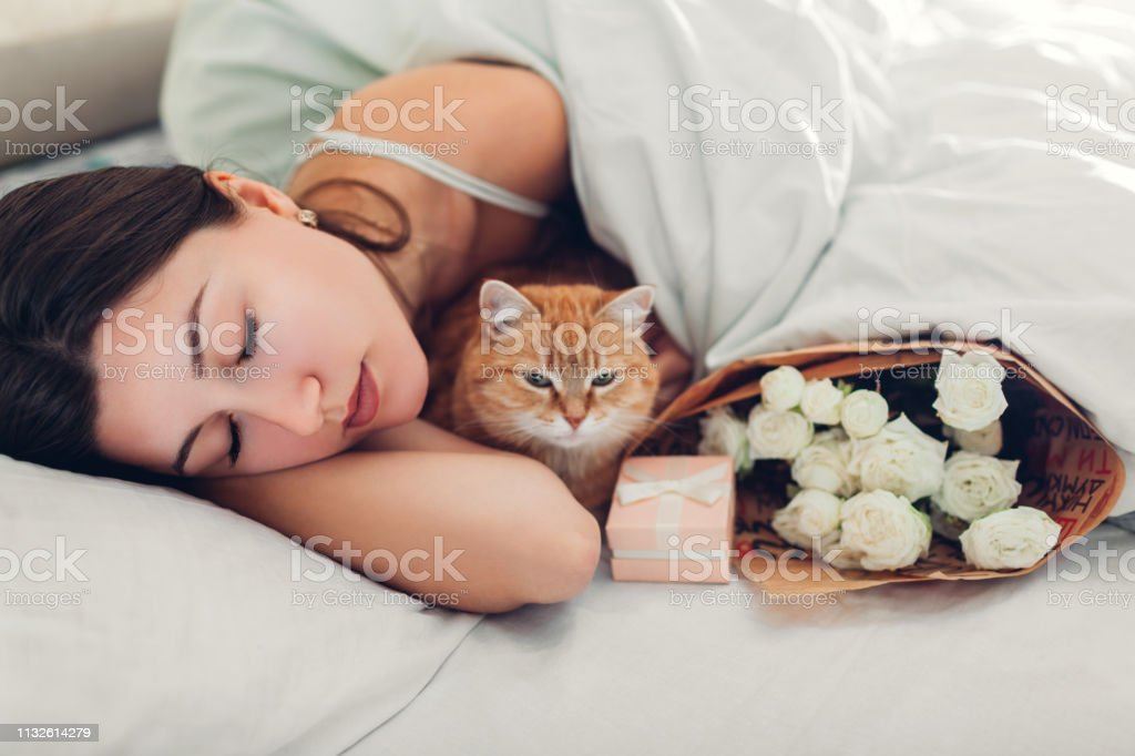 Young woman sleeping near bouquet of roses and gift box in bed with...