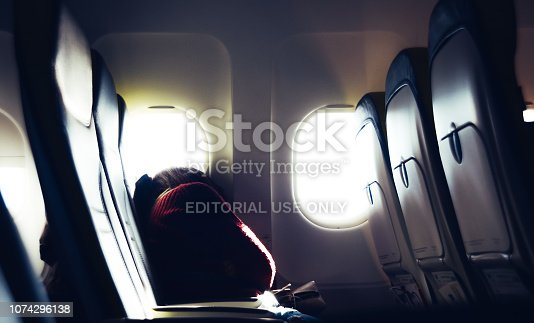 Up in the air - Nov 29, 2018: Tired casual unidentifiable millennial caucasian young woman napping on seat while traveling by airplane with bright light coming through windows - air travel concept.