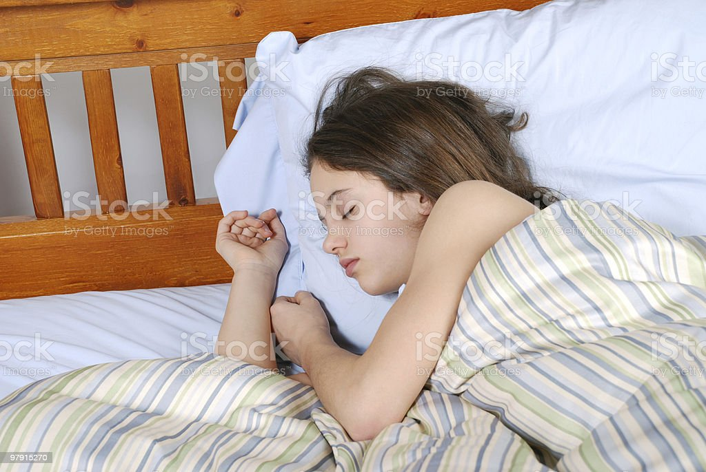 Young woman sleeping on her side in bed royalty-free stock photo