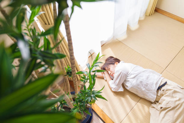 窓際で畳の上で寝ている若い女性 - 畳 ストックフォトと画像